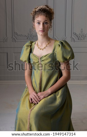 A young Regency woman in a silk dress sitting on a white chair  Royalty-Free Stock Photo #1949147314