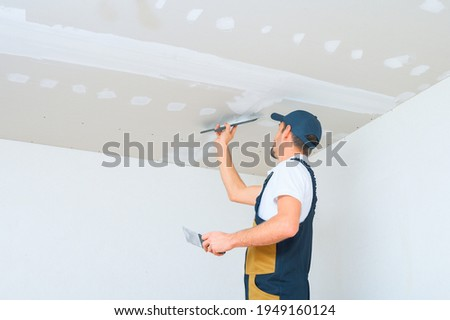 A uniformed worker applies putty to the drywall ceiling. Putty of joints of drywall sheets. Royalty-Free Stock Photo #1949160124