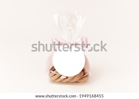Small gift with cookies in a plastic bag tied up to a bow with a pink ribbon and a round white gift tag attached