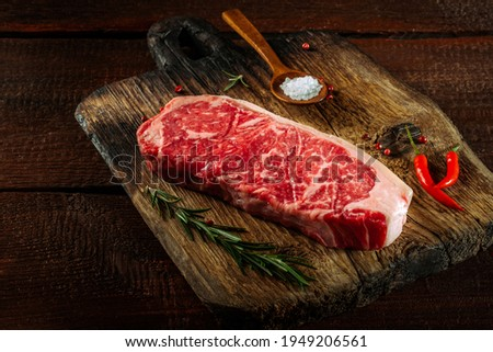 Raw striploin steak (New York) of beef on a board with seasonings, salt and red pepper Royalty-Free Stock Photo #1949206561