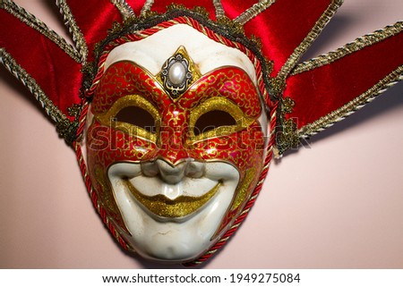 Venetian jester mask on a gold background, top view. Vintage joker mask.