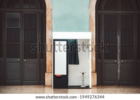 An indoor empty photo booth with open curtain, in between two wooden arch doors for creating photos for passport and other documents, with a blank template poster placeholder on the cabin wall