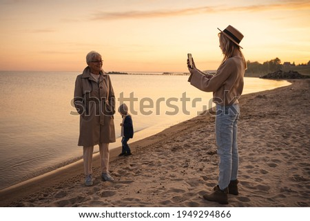 Adult daughter makes picture of her elderly mother on the beach