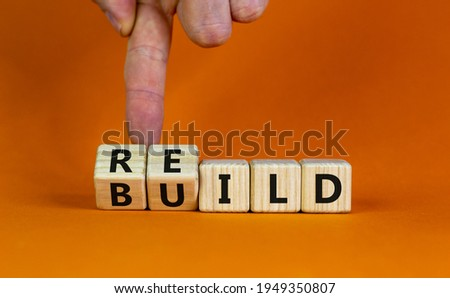 Rebuild symbol. Concept word 'rebuild' on wooden cubes on a beautiful orange table. Businessman hand. Orange background. Business and rebuild concept. Copy space. Royalty-Free Stock Photo #1949350807