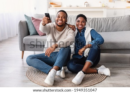 Leisure And Entertainment. Smiling African American couple watching TV show or film, guy holding remote control. Young man and woman enjoying free time sitting on floor carpet at home in living room Royalty-Free Stock Photo #1949351047