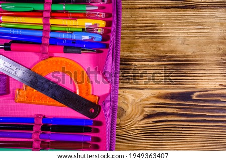 Different school stationeries (pens, pencils, felt tip pens, ruler and protractor) in pink pencil box. Top view