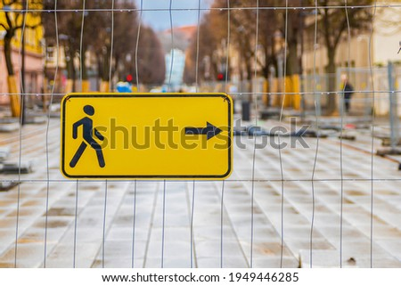 Building fence directing pedestrians. Yellow sign with the direction of pedestrian traffic, copy space