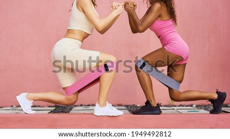 Photo fitness girls in a stylish sports suit squats with rubber bands on the background of a pink wall. Sports woman squats, sits. Copy ad space. Royalty-Free Stock Photo #1949492812
