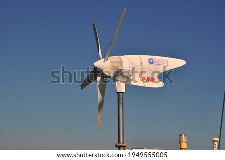 A photograph of a spinning white propellor used to generate power for a sail boat with blue clear sky in the background on Evia Island in Greece on a warm summer's evening.