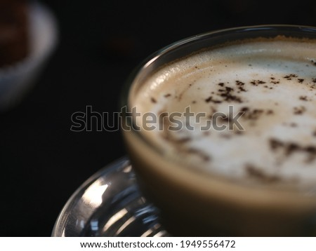 hot latte served in the glass on black background (Low-key Picture Style) ,hot coffee in a glass with cream poured over,hot drink  on a dark background
