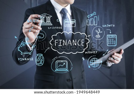 Businessman in formal suit is holding a tablet with a document and pointing a pen at an economic sketch with a bank, money, credit card and globe. The concept of management in financial business