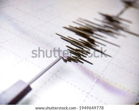 Richter scale Low and High Earthquake Waves with Vibration on white paper background, audio wave diagram concept, photo of cellphone screen, Aceh Indonesia Royalty-Free Stock Photo #1949649778
