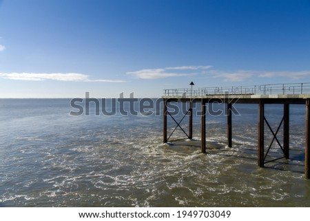 Coastal scenery at Heysham with turbulent water flowing round a jetty on a bright, sunny day Royalty-Free Stock Photo #1949703049