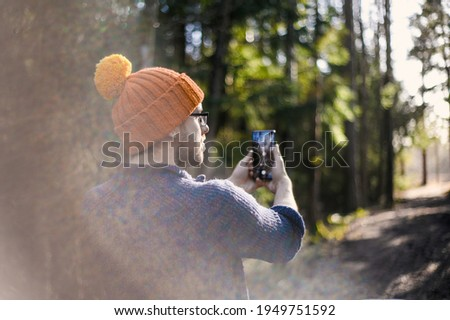 nerdy man with orange hat in the sunny spring Scandinavian forest with phone taking pictures of nature
