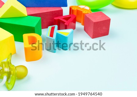 Bright toys for the child (soft construction kit, boat and car figurine, letters), pacifier on blue background. Space for text. The development of logic, thinking and motor skills in the baby.