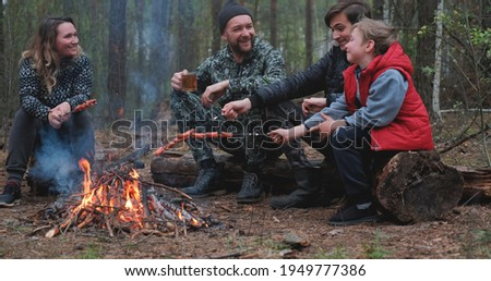 Family sits around a campfire on a summer evening. Children with parents are resting in the woods. Family frying sausages over a fire in the woods. Weekend in nature in good company.  Royalty-Free Stock Photo #1949777386