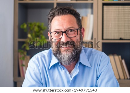 Portrait of one young and happy cheerful man smiling looking at the camera having fun. Headshot of male person working at home in the office.