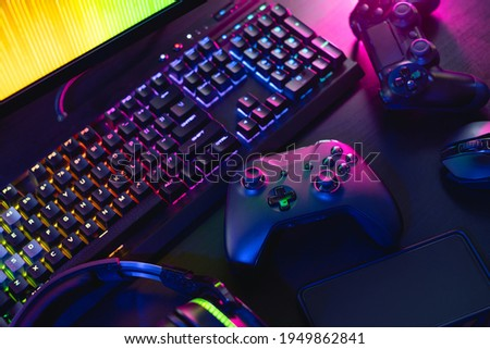gamer work space concept, top view a gaming gear, mouse, keyboard, joystick, and headset with rgb color on black table background. Royalty-Free Stock Photo #1949862841