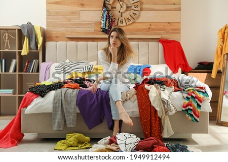 Young woman surrounded by different clothes in messy room. Fast fashion concept Royalty-Free Stock Photo #1949912494