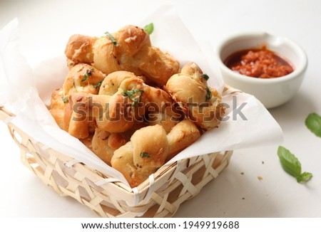 Home made garlic knots - strips of pizza dough tied in a knot, baked and then topped with melted butter, garlic and parsley. Served with marinara sauce Royalty-Free Stock Photo #1949919688