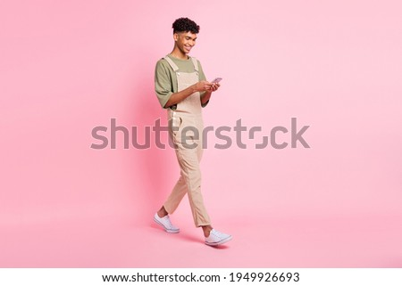 Full length body size photo of young man in overall smiling walking texting message on cellphone isolated on pastel pink color background