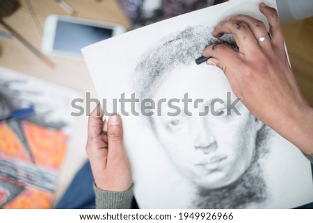 Top view of a close up of the hands of a person drawing a portrait in charcoal on a canvas. Concept of painting classes. Selective focus. Space for text.