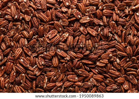 Pile of pecans, full-frame image, directly above view. Pecan nuts background. A multitude of Mexican pecan seeds. Delicious snacks. Dried food. Royalty-Free Stock Photo #1950089863