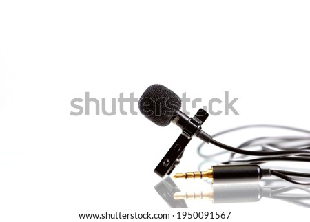 Small lavalier microphone or lapel mic on white background. Professional sound recording equipment for cell phone.