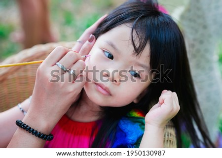 Close up of child sits with adult to paint cartoon on her face. Woman's hand holding a brush is drawing cute figure on an Asian girl's face. During Easter, summer or spring. Happy kid is 4 years old.
