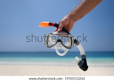 A man holds a snorkel mask in his hand against a clear blue sky and turquoise ocean. Diving mask in a man's hand. Photo of a mask and snorkel for swimming in a pool or sea with a central composition Royalty-Free Stock Photo #1950153262