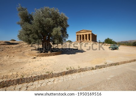 Temple of Concordia, or Tempio della Concordia in Italian. Barren landscape with a single olive tree and statue of Ikarus. Valley of Temples, Agrigento, Sicily, Italy. Selective focus.