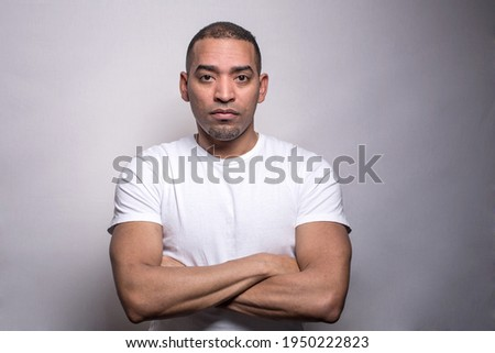 A portrait of a Hispanic middle age athletic man in a white t-shirt, serious, crossed hands, isolated on the grey background Royalty-Free Stock Photo #1950222823