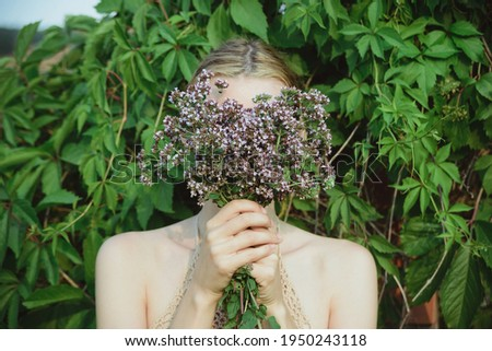 woman hold fresh cutting oregano plant bouquet and and hide face on green leaves background, horizontal lifestyle outdoors summer floral and botanical stock photo image