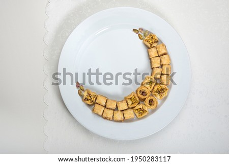 Baklava - A popular Middle Eastern sweet, arranged in a moon shape. Conceptual photo for Eid special sweets and dessert.