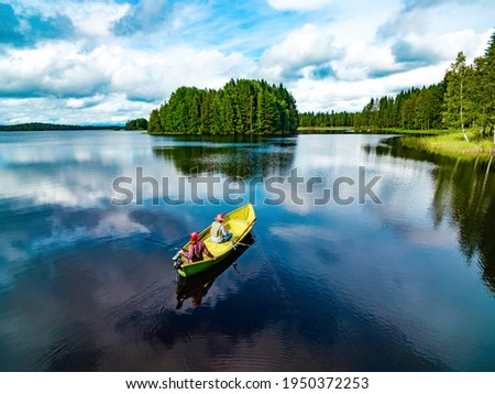 Aerial view of fishing boat with young woman and man in blue summer lake in Finland Royalty-Free Stock Photo #1950372253