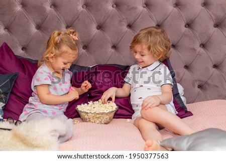 Happy children watching 3D movie with glasses and popcorn.