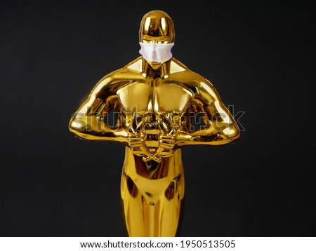 Hollywood Golden Oscar Academy award statue in medical mask on black background. Success and victory concept. Oscar ceremony in coronavirus time