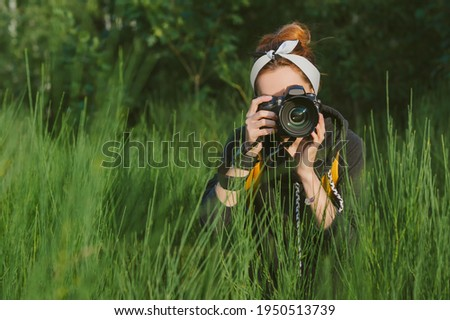 A girl photographer is holding a professional photo-video camera in her hands. Against the backdrop of beautiful green nature and forests