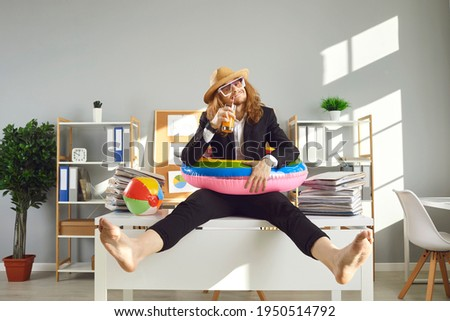 Annual leave and planning travel vacation concept. Funny office worker waiting for summer holidays. Happy barefoot employee in sun hat, sunglasses and swim ring sitting on desk and drinking cocktail Royalty-Free Stock Photo #1950514792