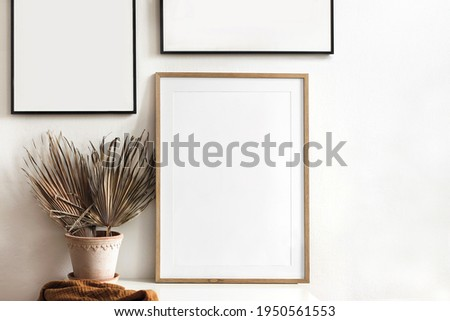 Set of  black portrait picture frame mockups. Dry palm leaves in flower pot and rusty linen textile on table. White wall background. Boho exotic interior design. Living room. Neutral color palette.