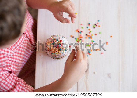 top view of Easter cake decorate children's hands with decorative dusting. Easter cake in the hands of a child on the background of a white wooden table. Royalty-Free Stock Photo #1950567796