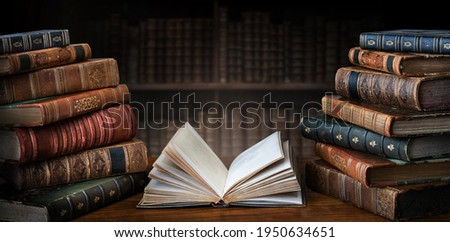 Opened book and stacks of old books on wooden desk in old library. Ancient books historical background. Retro style. Conceptual background on history, education, literature topics. Royalty-Free Stock Photo #1950634651