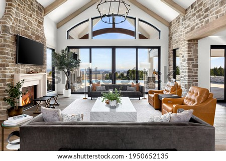 Beautiful living room in new traditional  luxury home. Features stone accents, vaulted ceilings, fireplace with roaring fire, and gorgeous exterior view of infinity pool and valley. Royalty-Free Stock Photo #1950652135