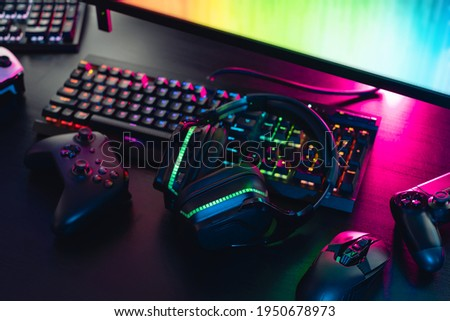 gamer work space concept, top view a gaming gear, mouse, keyboard, joystick, headset with rgb color on black table background. Royalty-Free Stock Photo #1950678973