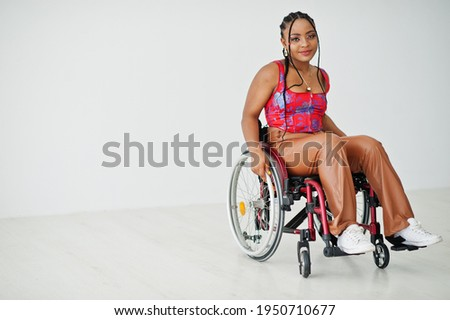 Young disabled African American woman in wheelchair against white wall. Royalty-Free Stock Photo #1950710677
