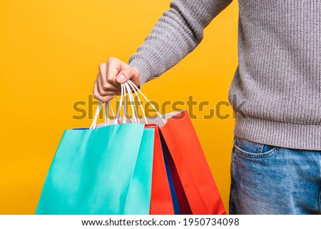 It's shopping time! Happy bearded happy young man with colorful paper bags isolated over yellow background.