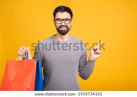 It's shopping time! Happy bearded happy young man with colorful paper bags isolated over yellow background. Pointing finger.