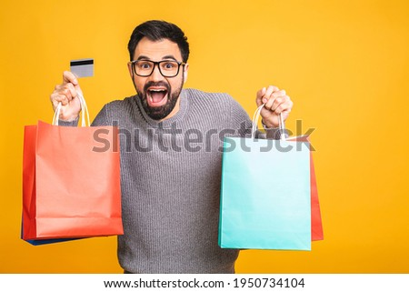 It's shopping time! Happy bearded happy young man with colorful paper bags isolated over yellow background. Using credit card.