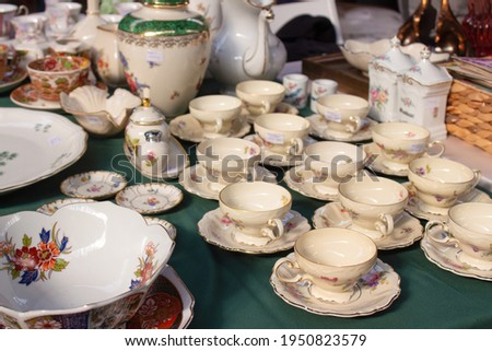 Antiques on flea market or festival - vintage porcelain tea cups, tableware and other vintage things. Collectibles memorabilia and garage sale concept. Selective focus Royalty-Free Stock Photo #1950823579