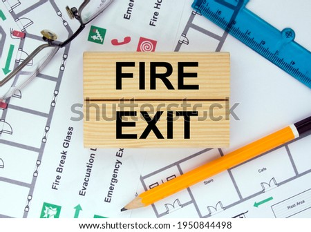 Wooden blocks with text Fire Exit Architectural design, sketch, drawing paper, drawings, simple pencil, eyeglasses with protractor on the table